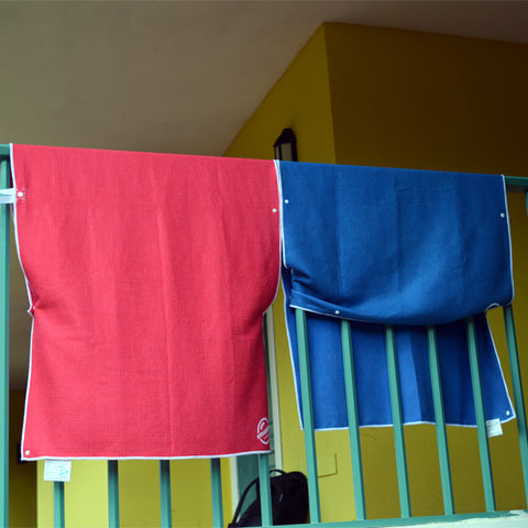 Microfiber Travel Swim towels snapped to balcony railing so that they can dry quickly without blowing away or needed clothes pins. Also great in a hostel or on a boat.