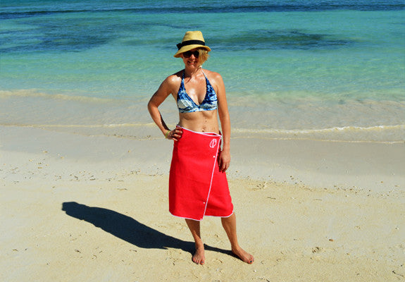 Woman wearing a pink Snappy Towel wrapped and snapped on her waist as a wrap or kilt. Snaps on at the beach, pool or at home.