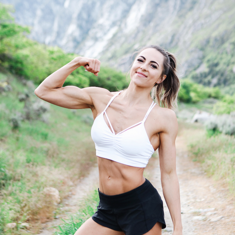 girl in mountains flexing a muscle