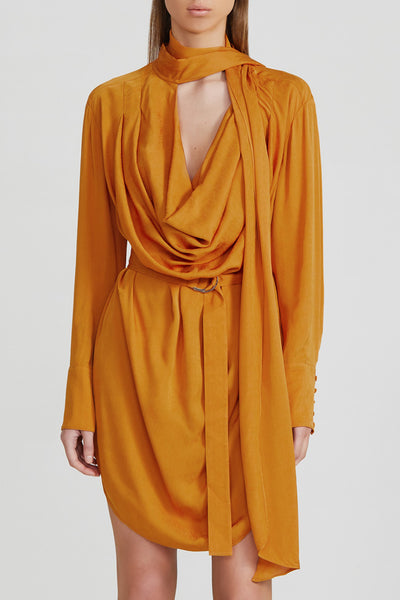 Acler turmeric orange mini dress with fitted waist, drape v-neckline, neck tie detail, adjustable d-ring wrap, long balloon sleeves with wide cuff with drape detail and curved hem in lightweight satin fabrication