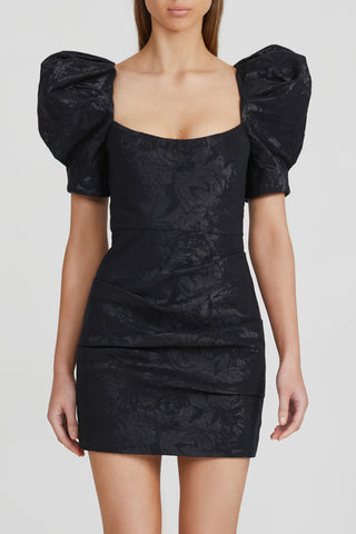 Acler black mini dress with fitted waist, square neckline, textured jacquard fabrication, puff short sleeves and open back with rouleau tie detail