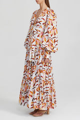 Acler white maxi dress with orange floral pattern, fitted waist with twist detail, balloon sleeves, v-neckline and tiered full skirt in exclusive print