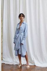 Acler cornflour blue midi dress with fitted waist, drape v-neckline, collar, wide cuff detail, wrap like detail at waist, relaxed sleeves, curved hemline and side split with inbuilt waist belt in lightweight fabrication