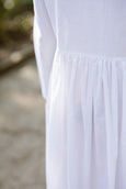 Woman wearing white cotton petticoat with long sleeves, up close image from the back