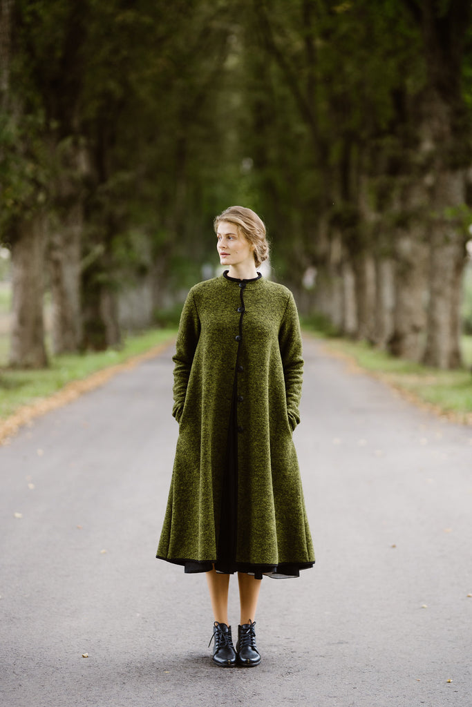 Woman wearing green color long wool coat, image from the front