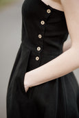 Woman wearing black sleeveless dress, up close image of a pocket.
