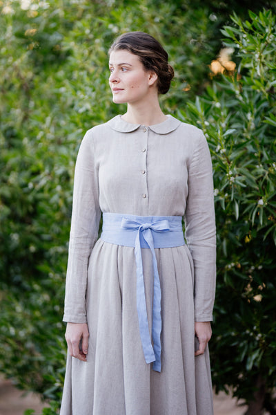 Woman in classic linen dress with sky blue waist belt