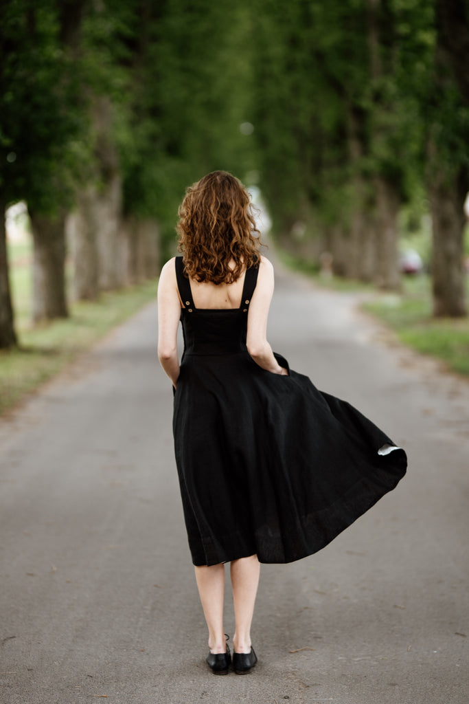 Woman wearing black sleeveless dress, picture from the back.