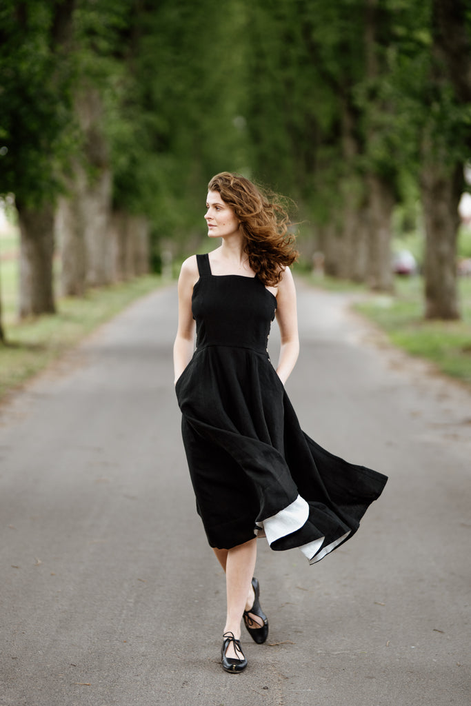 Model wearing black sleeveless dress, image from the front.