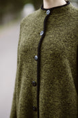 Woman wearing green color long wool coat, up close image from the front