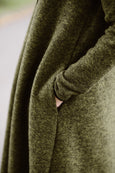 Woman wearing green color long wool coat, up close image of a pocket