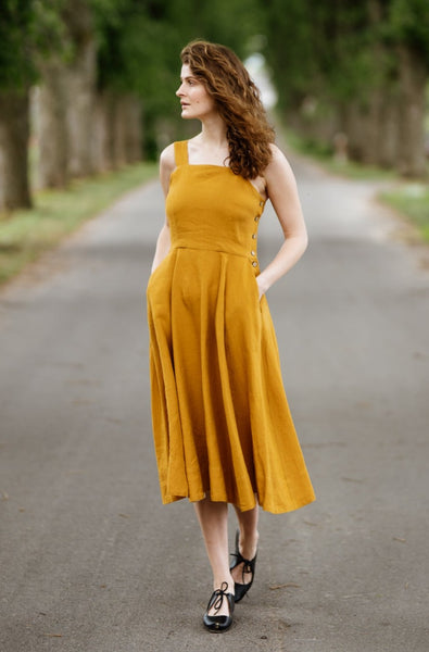 Woman wearing yellow color sleeveless dress, picture from the front.