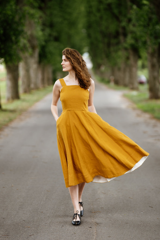 Woman wearing yellow color sleeveless dress, image from the front.