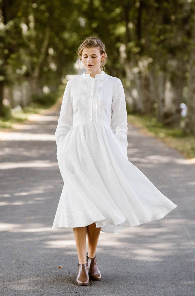 Model wearing white dress with long sleeves, image from the front.
