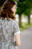 Woman wearing linen floral dress, image from the back.