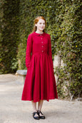 Woman wearing red color classic dress with long sleeves, picture from the front.