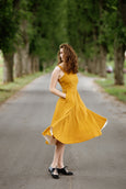 Woman wearing yellow color sleeveless dress, image from the side.