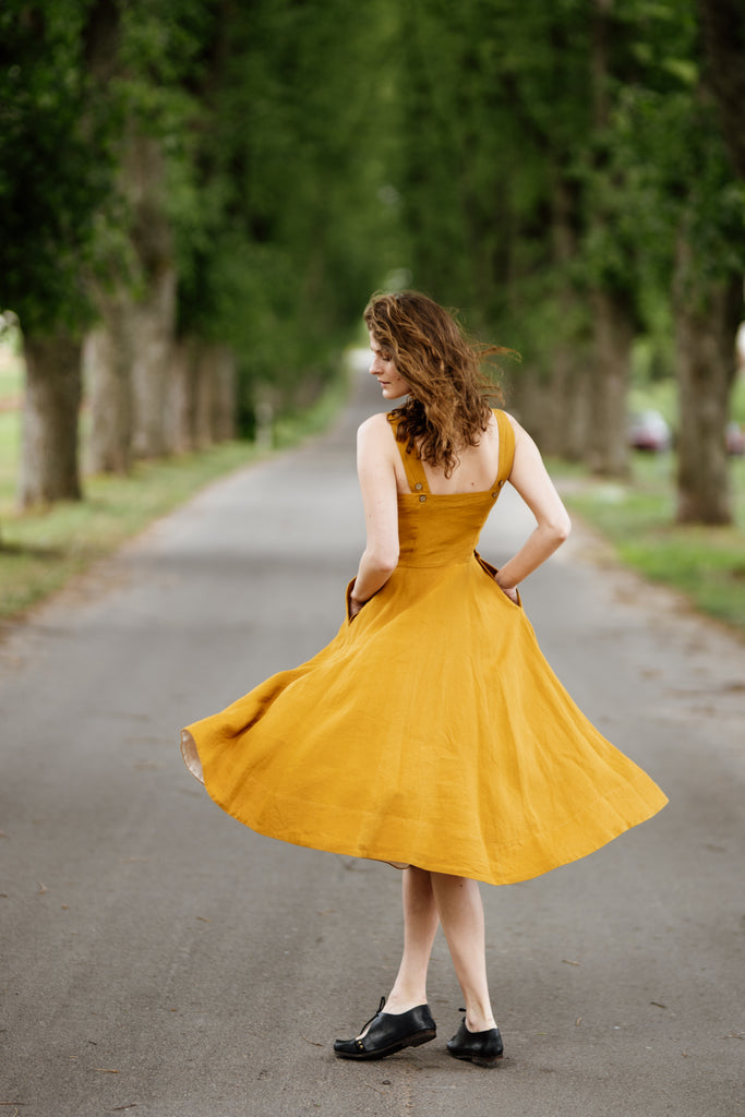 Woman wearing yellow color sleeveless dress, image from the back