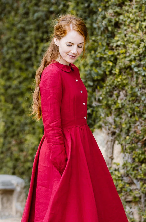 Woman wearing red color classic dress with long sleeves, picture from the side.