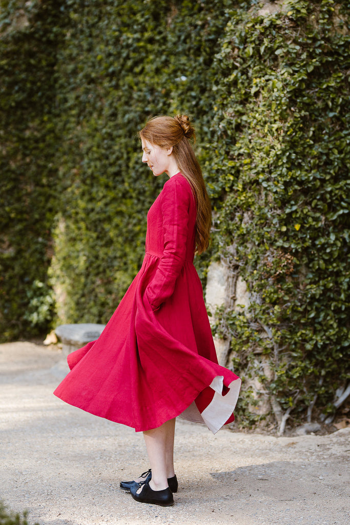 Model wearing red color classic dress with long sleeves, picture from the side.