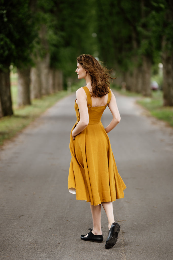 Woman wearing yellow color sleeveless dress, picture from the back.