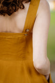 Woman wearing yellow color sleeveless dress, up close image from the back.