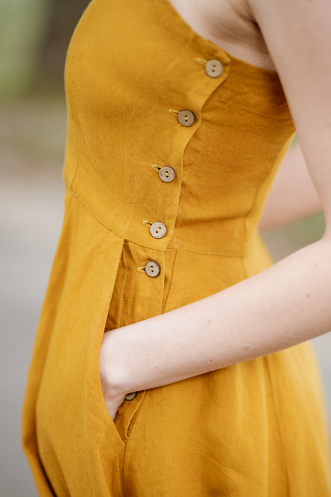 Woman wearing yellow color sleeveless dress, up close image from the side.