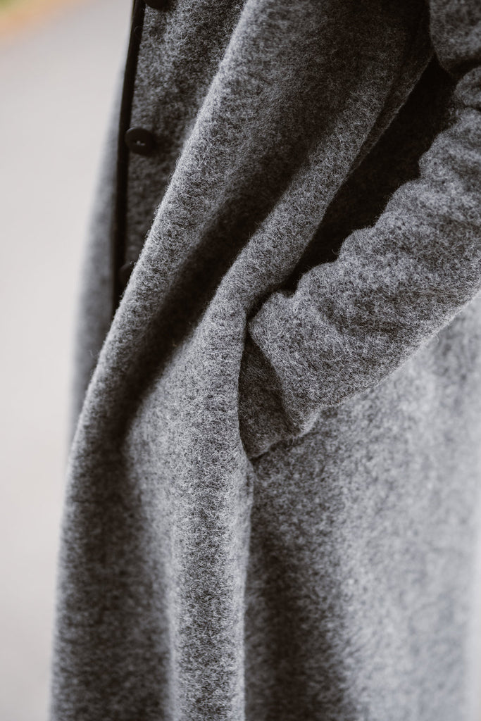 Woman wearing grey color long wool coat, up close image of a pocket