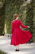 Woman wearing red color classic dress with long sleeves, image from the back.