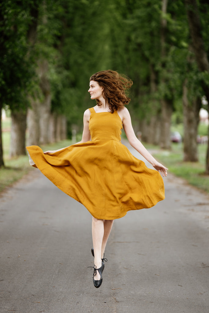 Model wearing yellow color sleeveless dress, picture from the front.