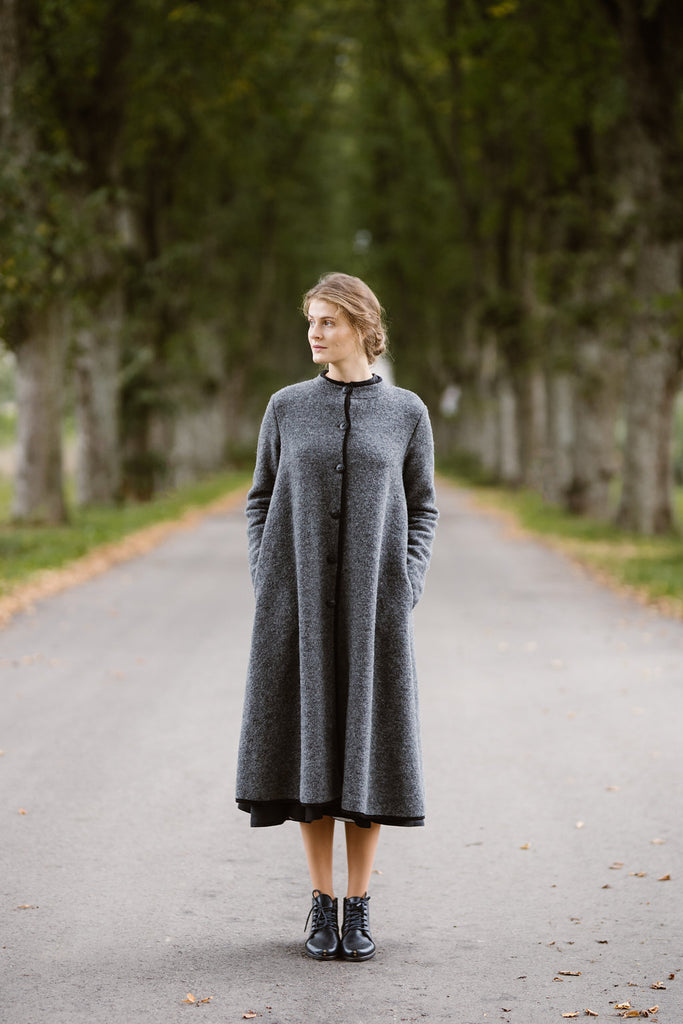 Woman wearing grey color long wool coat, picture from the front
