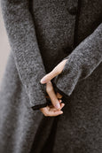 Woman wearing grey color long wool coat, up close image from the front