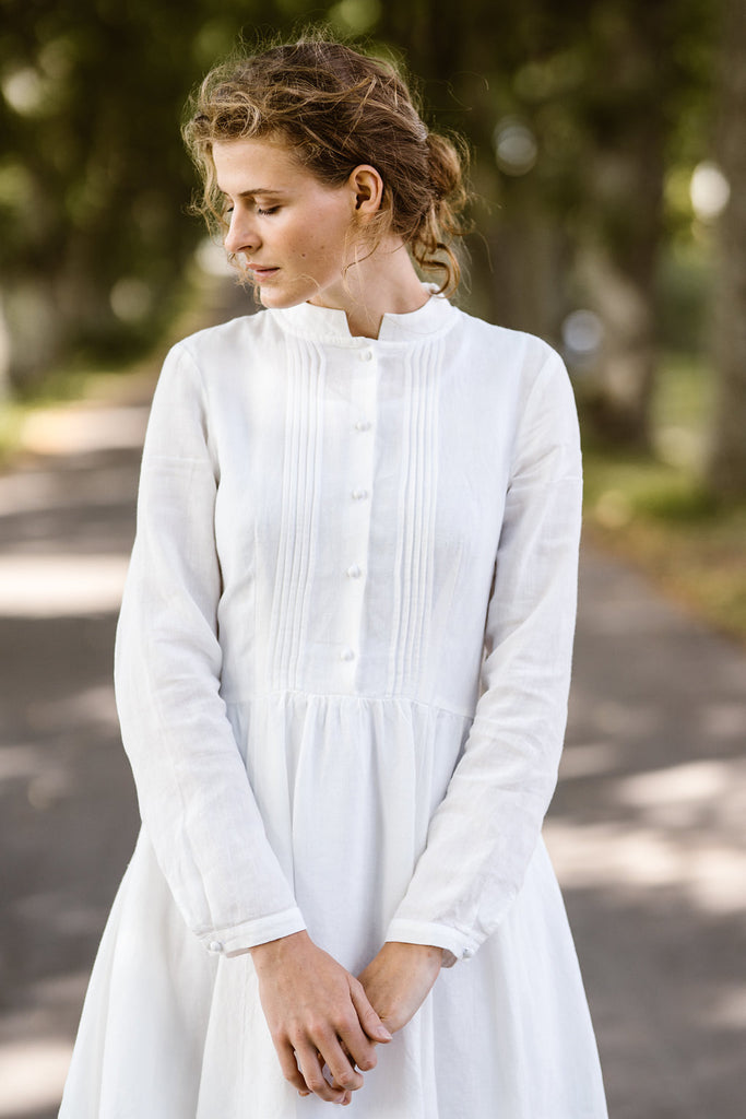 Woman wearing white dress with long sleeves, picture from the front.