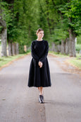 Woman in black soft linen dress, below the knee length