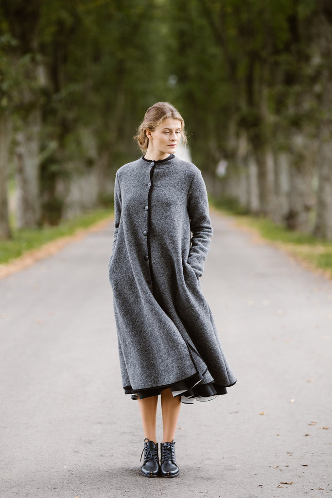 Woman wearing grey color long wool coat, image from the front