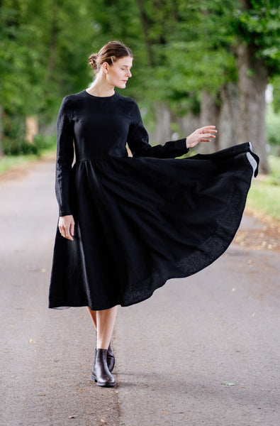 Woman in a black linen dress with long sleeves