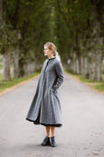 Woman wearing grey color long wool coat, image from the side