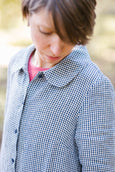 Woman wearing checkered blue and white color button down dress with long sleeves, up close image from the side.