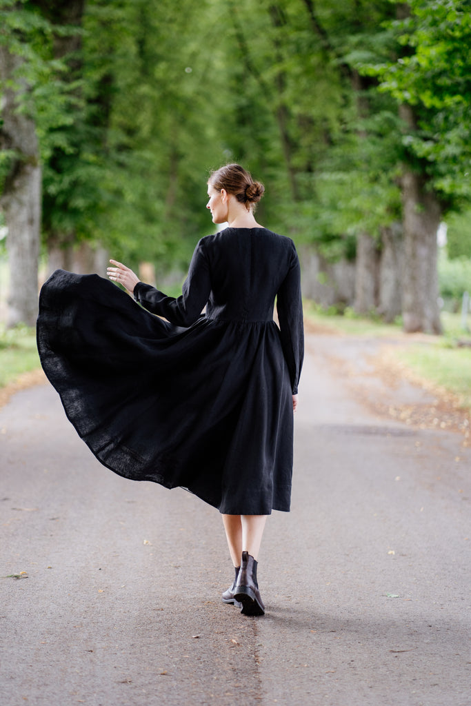 Woman pictured from the back in black linen dress