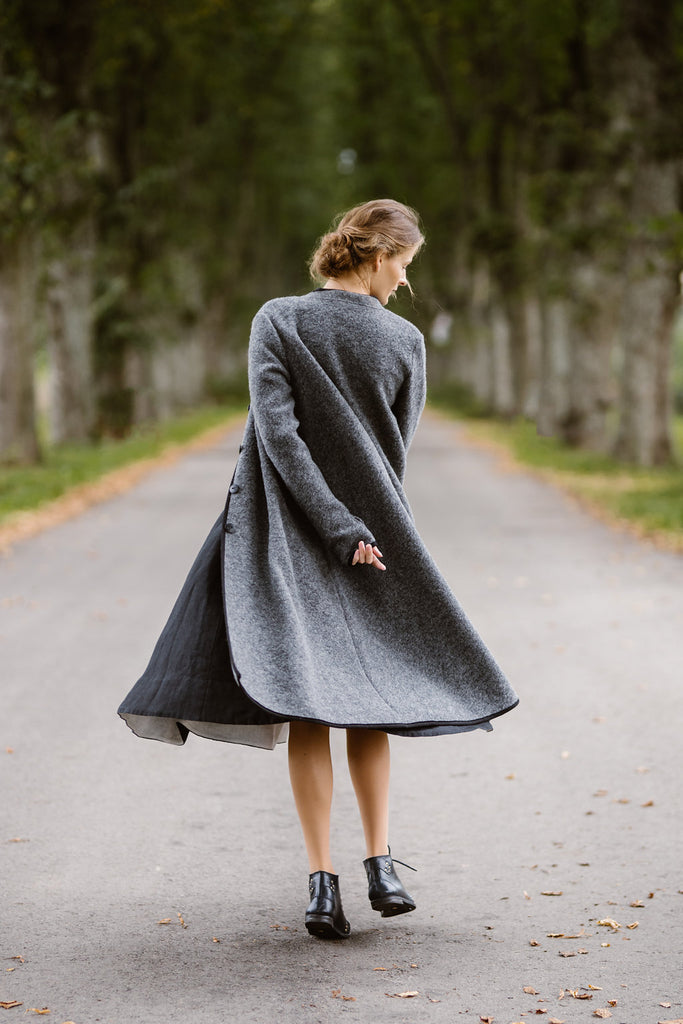Woman wearing grey color long wool coat, image from the back