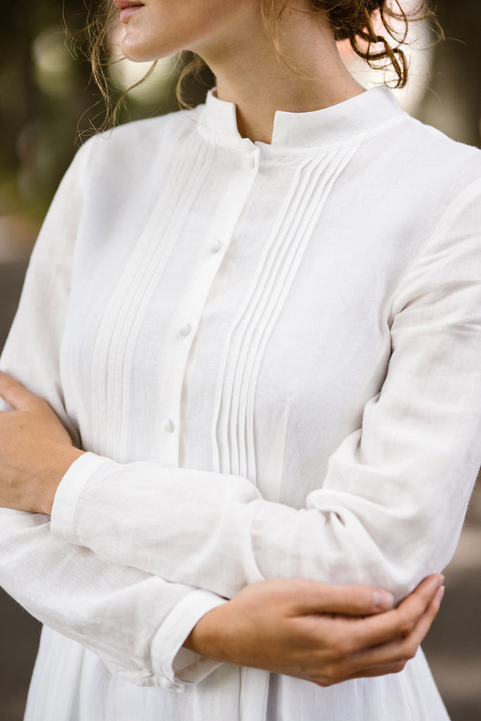 Woman wearing white dress with long sleeves, up close image from the front.