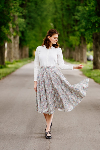 Woman in a linen floral print skirt matched with white shirt.
