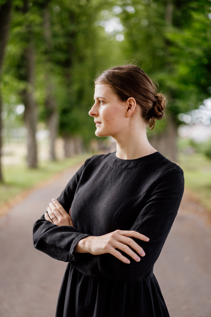 Woman in organic black linen dress with long sleeves
