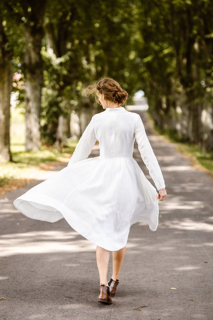 Woman wearing white dress with long sleeves, picture from the back.