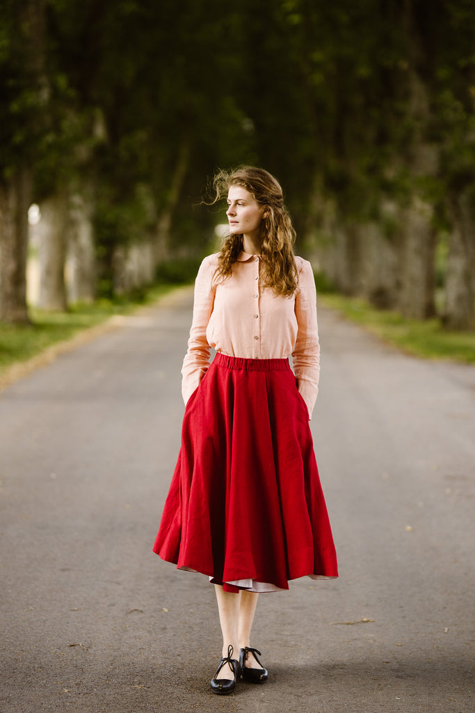 Woman wearing red color linen midi skirt, image from the front