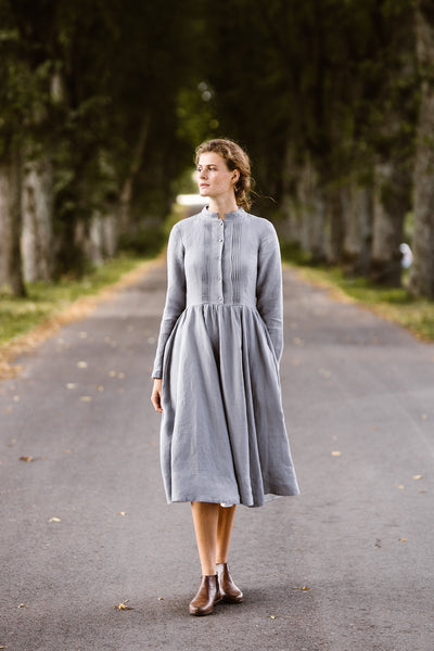 Woman wearing grey dress with long sleeves, image from the front