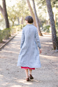Woman wearing checkered blue and white color button down dress with long sleeves, picture from the back.