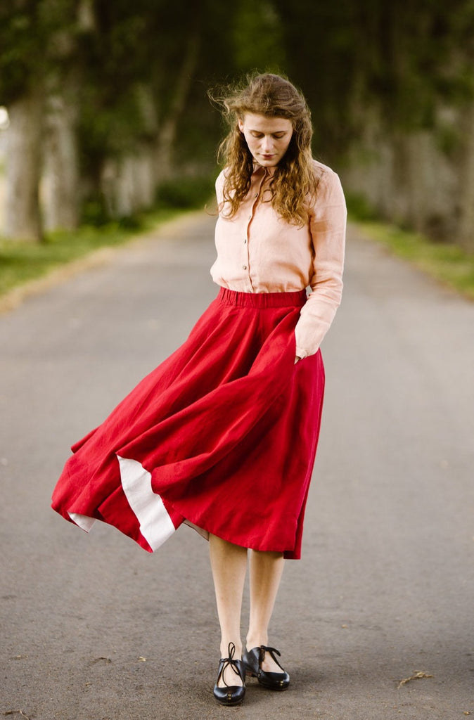 Woman wearing red color linen midi skirt, picture from the front