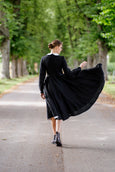 Woman pictured from the back in a black linen dress