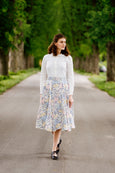 Woman in floral print linen skirt and white linen shirt.